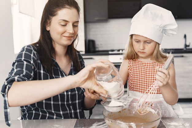 Family in a kitchen cook the dough for cookies