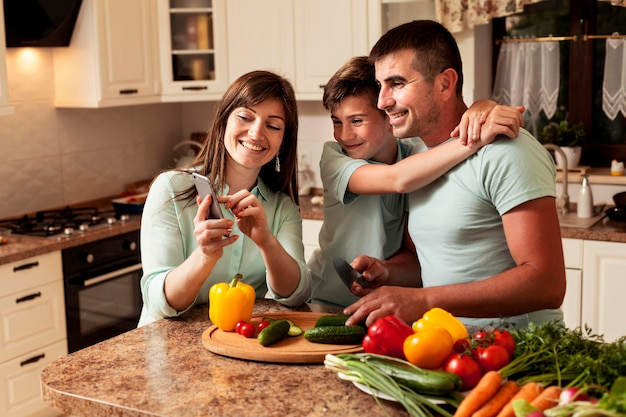 Family in the kitchen looking at pictures on smartphone
