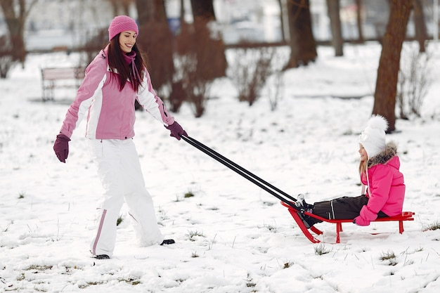 Family in knitted winter hats on family christmas vacation. woman and little girl in a park. people playing with sled.