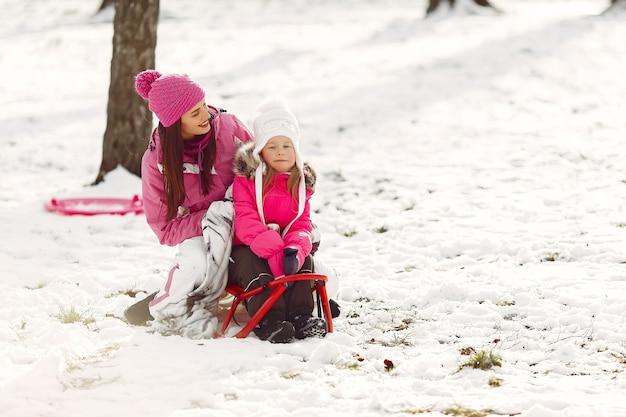 Famiglia in cappelli invernali lavorati a maglia in vacanza di natale in famiglia. donna e bambina in un parco. persone che giocano con la slitta.