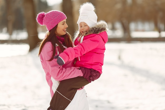 Family in knitted winter hats on family christmas vacation. woman and little girl in a park. people playing.