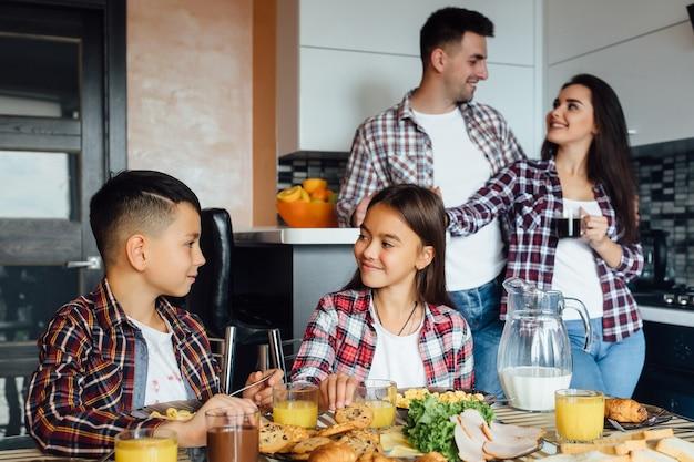 식사를 하는 동안 부엌에서 아침 식사를 둘러싸고 웃고 있는 가족과 함께 앉아 있는 동안 서로를 바라보는 아이들.