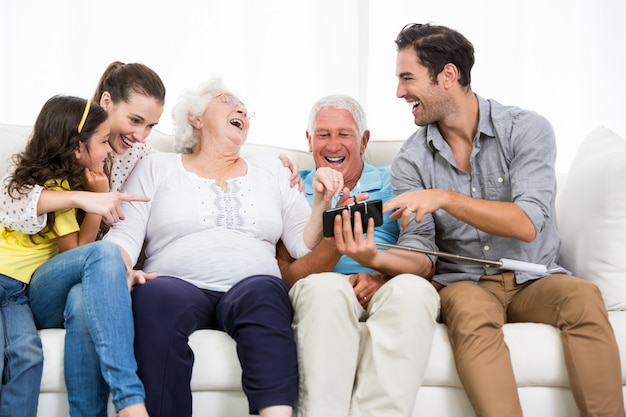Family laughing while looking at smartphone photos