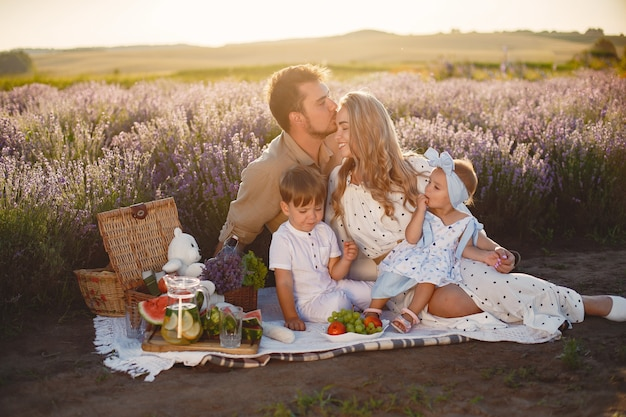 Family on lavender field. people on a picnic. mother with children eats fruits.