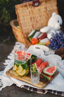 Famiglia sul campo di lavanda. persone a un picnic. la madre con i bambini mangia la frutta.