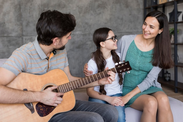 Family learning to play guitar