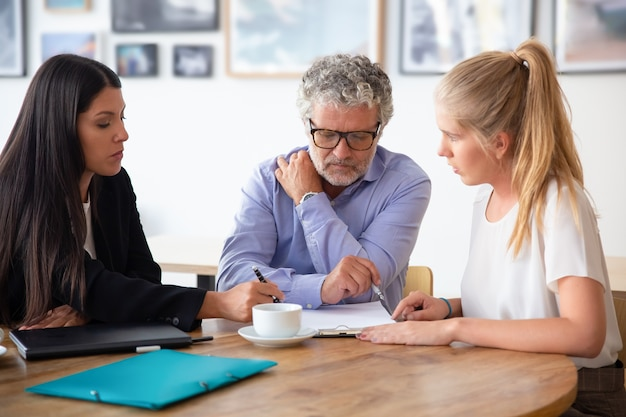 Family legal advisor explaining document details to mature father and adult daughter