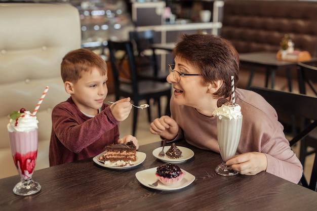 Семейный отдых и развлечения. счастливая бабушка с короткими волосами, очки и внук отдыхают в кафе. они едят пирожные с молочными коктейлями и угощают друг друга