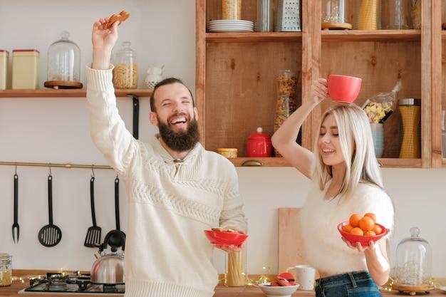 家族のレジャーと楽しみ。マンダリンとクッキーとモダンなキッチンでダンスを楽しんで幸せなカップル。
