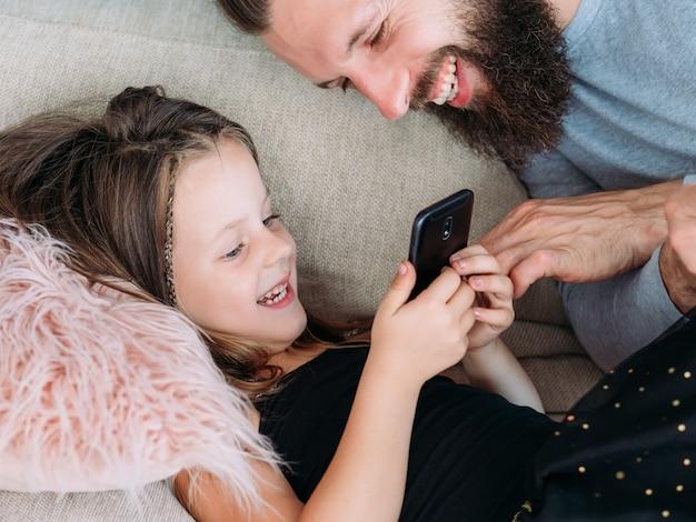 家族のレジャー。パパと彼の小さな女の子が携帯電話で面白いクリップを見ています。喜びと笑い。幸せな関係。父と子のコミュニケーション。
