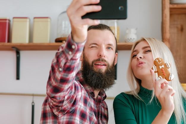 Семейный досуг. веселая пара с помощью камеры смартфона, чтобы сделать селфи с пряничным человечком.