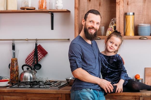 Семейный досуг. счастливый отец и его милая маленькая дочь наслаждаются проведением времени вместе на домашней кухне.