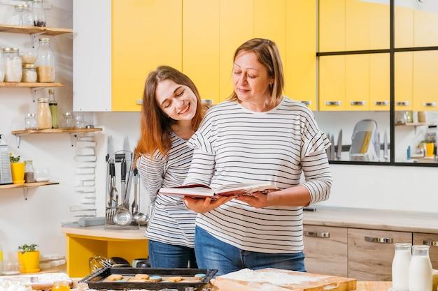 부엌에서 가족 레저. 엄마와 딸이 함께 요리를 즐기고 요리 책의 레시피와 결과를 비교합니다.