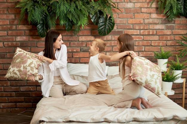 家族のレジャー。ママの息子と娘は寝室のベッドの枕で戦う。喜びと楽しさ