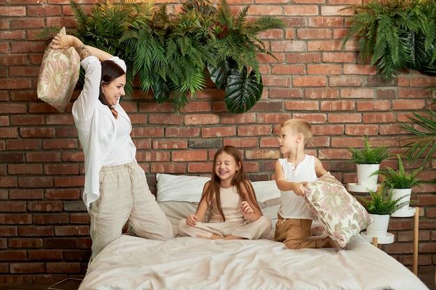 가족 여가. 엄마 아들과 딸은 침실의 침대에 베개를 놓고 싸 웁니다. 기쁨과 즐거움