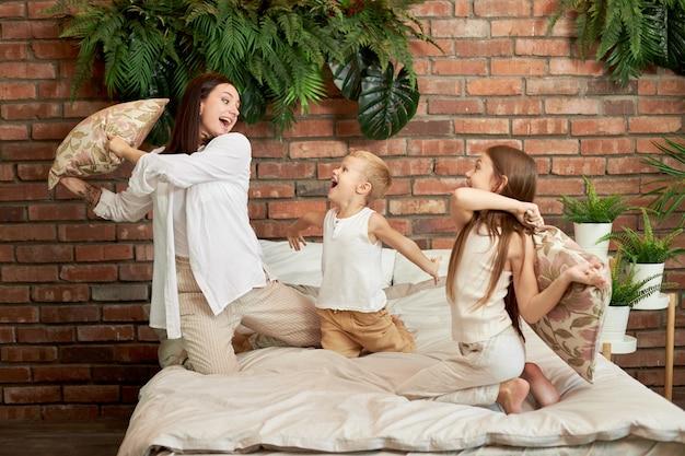 가족 여가. 엄마 아들과 딸은 침실의 침대에 베개를 놓고 싸 웁니다.