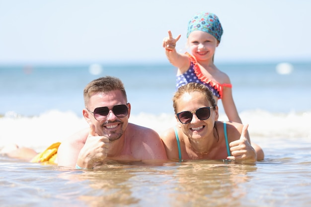 The family lies on seashore and holds thumb up.