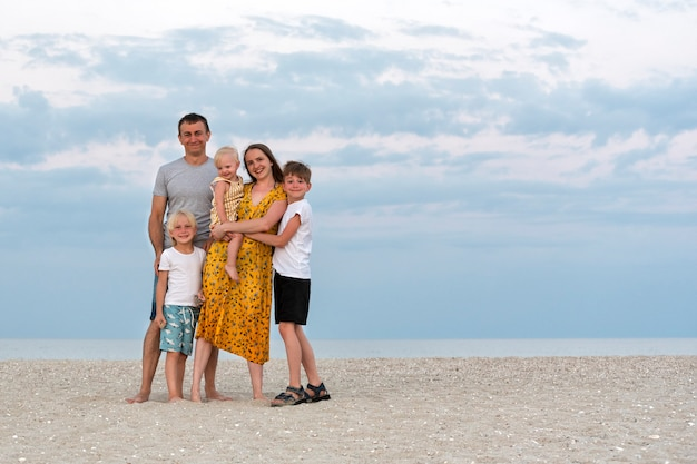 Family lifestyle. family holidays together. father, mother and tree child on sea and sky background.