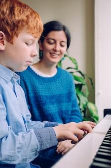 실내에서 함께 시간을 보내는 가족 생활. 음악적 미덕과 예술적 호기심을 가진 아이들. 교육적인 음악 활동. 집에서 피아노 레슨을 어린 소년을 가르치는 피아노 교사 여자.