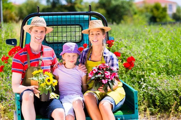 Family on light truck with flowers in garden
