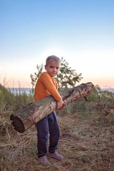 Семейный отдых. ребенок собирает деревянные дрова для костра в кемпинге, активный образ жизни