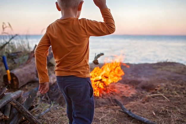 Семейный отдых. ребенок смотрит на огонь перед ночевкой в кемпинге, активный образ жизни