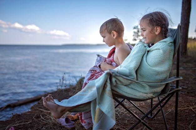 Семейный отдых. дети смотрят на море мокрые после купания в кемпинге, активный образ жизни