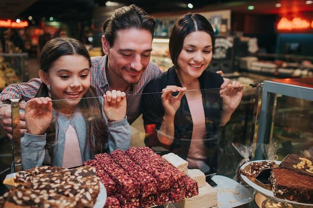 Семья смотрит на вкусные конфеты и сладости и улыбается
