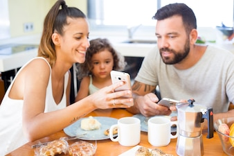Family looking at mobile phone screen during breakfast