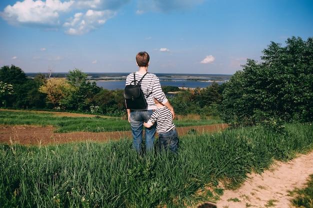 遠くから大きな川を見ている家族