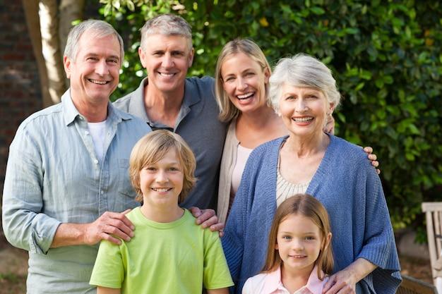 Семья, глядя на камеру в саду