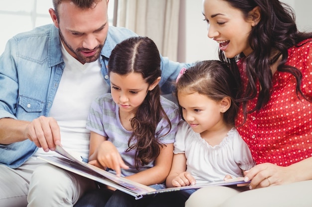 Family looking in picture book while sitting on sofa