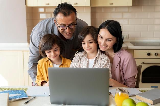 Семья смотрит вместе на ноутбуке дома