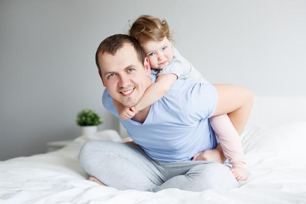 Концепция дня семьи, любви и отца - портрет счастливого молодого отца и его милой маленькой дочери, весело проводящих время дома