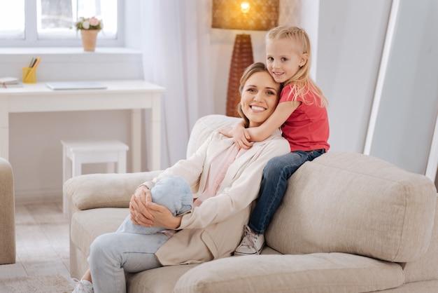가족 사랑. 소파에 앉아 그녀와 함께 집에있는 동안 그녀의 어머니를 포옹 귀여운 멋진 웃는 소녀