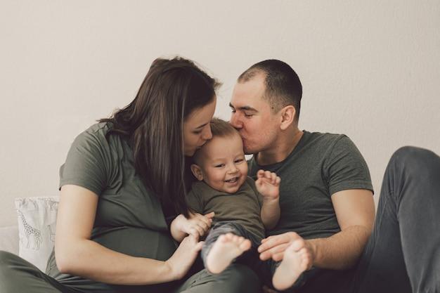 Семейная любовь. родители и маленький сын, весело вместе дома в спальне.