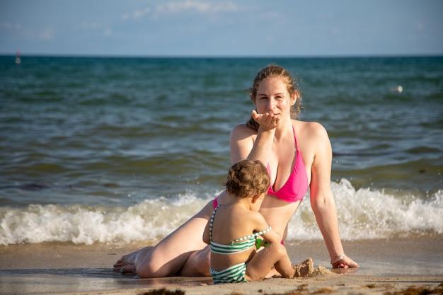 가족 사랑 젊은 엄마와 아기 유아는 해변에서 모래에서 놀고 엄마는 보내