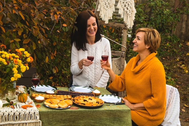 Семейный обед на заднем дворе. женщины-мужчины пьют вино и смеются.