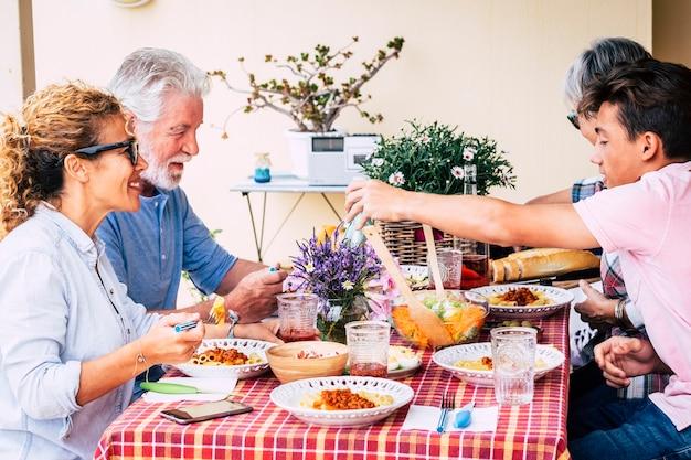 混合年齢の白人グループと一緒に家族のランチタイムは、時間を楽しんで、テーブルで食事をします