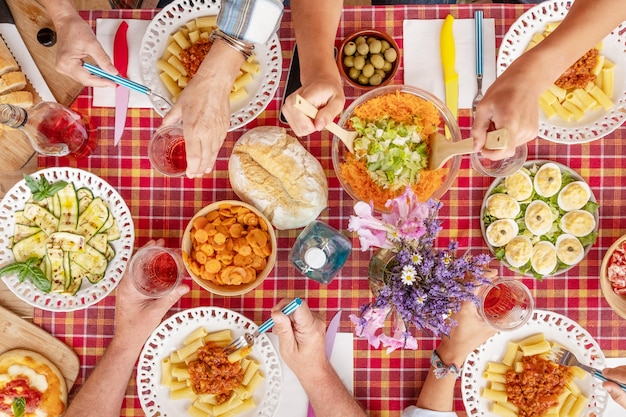 Family lunch with a colorful checked tablecloth many hands that take food