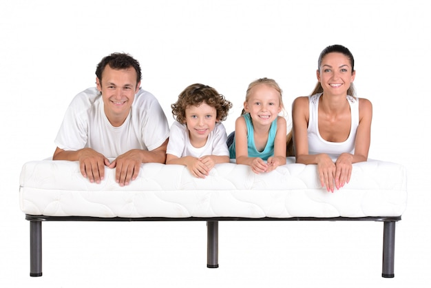Family lying on mattresses, isolated