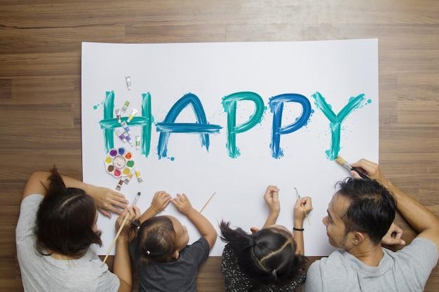 家庭の彼女の部屋で紙の上にペイン幸せな言葉を塗っている家族、トップビュー