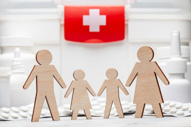 가족 약. 아빠, 엄마, 딸, 아들은 약을 배경으로 손을 잡고 있습니다.