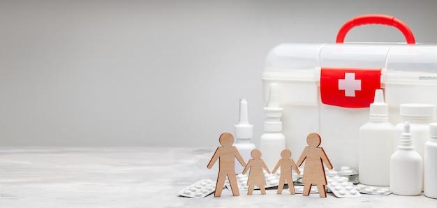 Семейная медицина. семья с детьми на фоне аптечки и лекарств с таблетками.
