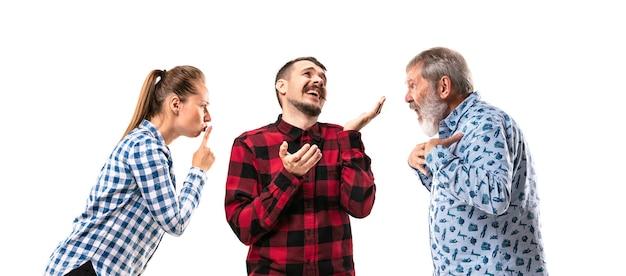 Члены семьи спорят друг с другом на белом фоне студии. понятие человеческих эмоций, выражения, конфликта поколений. женщина и мужчина в споре. поясной портрет. copyspace.