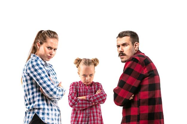 Члены семьи спорят друг с другом на белом фоне студии. понятие человеческих эмоций, выражения, конфликта поколений. женщина, мужчина и маленькая девочка. детские обиды, рассерженные родители.