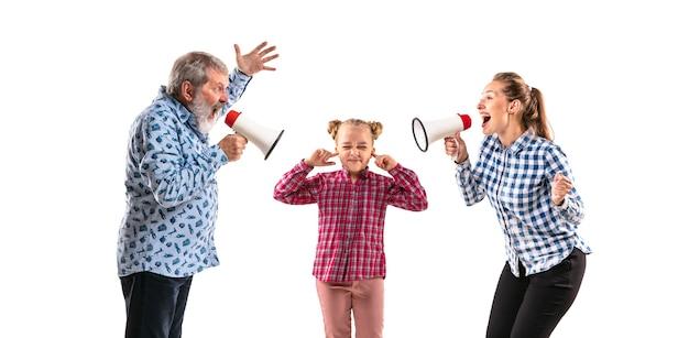 Члены семьи спорят друг с другом на белом фоне студии. понятие человеческих эмоций, выражения, конфликта поколений. женщина, мужчина и маленькая девочка. родительские скандалы, детские проблемы.