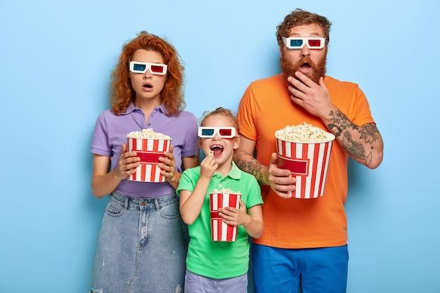 家族はポップコーンでテレビを見ることを楽しんでいます