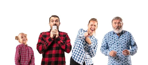 Члены семьи смеются и указывают друг на друга на белом фоне студии. понятие человеческих эмоций, выражения, различия поколений. женщина, мужчины и маленькая девочка. разные эмоции.