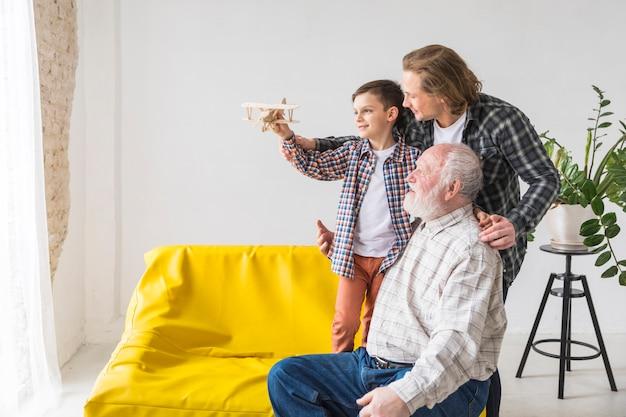 さまざまな世代の家族の男性が模型飛行機を持っています。